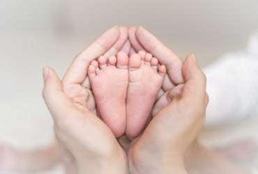 Close up of newborn baby feet on female hands